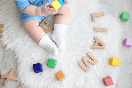 Foto de Cute baby sitting on floor with word LIAM composed of wooden letters. Choosing name concept - Imagen libre de derechos