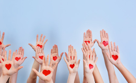 Photo pour Raised in air hands with drawn hearts on palms against light background. Volunteering concept - image libre de droit