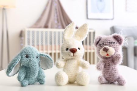 Foto de Adorable crochet baby toys on table in bedroom - Imagen libre de derechos