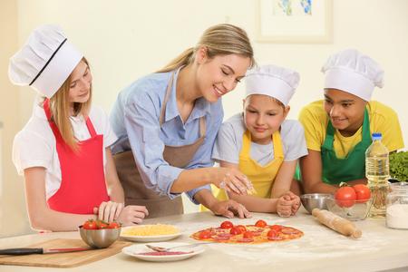 Foto de Group of children and teacher in kitchen during cooking classes - Imagen libre de derechos