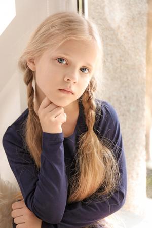 Photo pour Cute little girl near window at home - image libre de droit