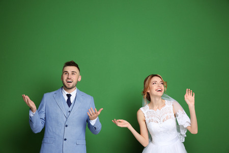 Foto de Happy wedding couple on color background - Imagen libre de derechos