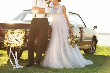 Photo pour Happy wedding couple near decorated car on shore - image libre de droit