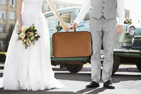 Foto de Happy wedding couple with suitcase and car outdoors - Imagen libre de derechos