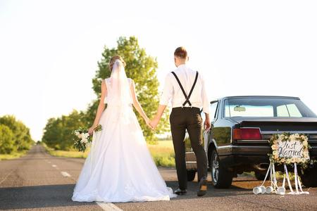 Foto de Happy wedding couple near decorated car outdoors - Imagen libre de derechos