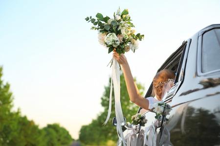 Photo pour Beautiful young bride holding bouquet in decorated car - image libre de droit