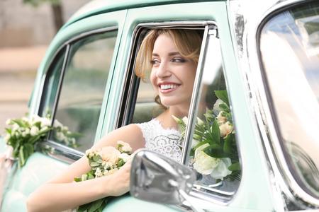 Foto de Beautiful young bride in decorated car - Imagen libre de derechos
