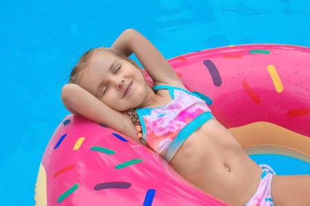 Photo pour Cute little girl on inflatable donut in swimming pool - image libre de droit
