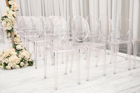 Foto de Transparent plastic chairs for guests on wedding ceremony - Imagen libre de derechos