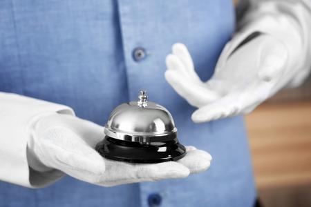 Photo pour Man holding bell on blurred background, closeup - image libre de droit