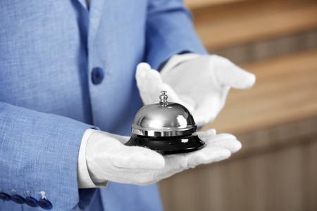 Photo pour Man holding bell on blurred background - image libre de droit