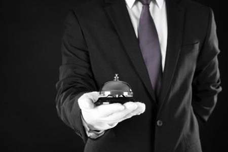 Photo pour Man holding bell on black background, closeup - image libre de droit