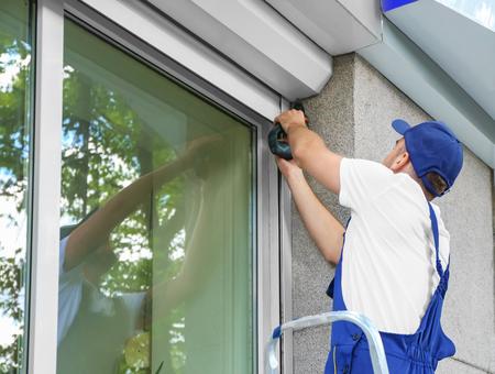 Photo pour Man installing roller shutter on window - image libre de droit