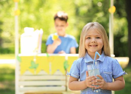 Photo pour Adorable girl holding glass of lemonade in park - image libre de droit