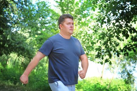 Foto de Overweight man running in green park - Imagen libre de derechos