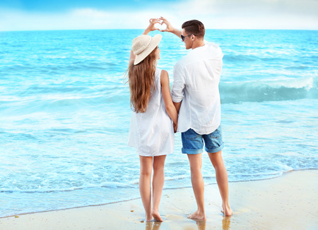 Photo pour Happy young couple making heart with their fingers on sea beach - image libre de droit