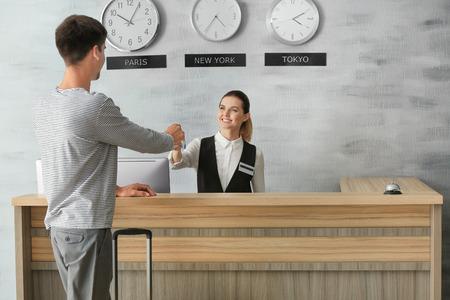 Foto de Young man at reception desk in hotel - Imagen libre de derechos