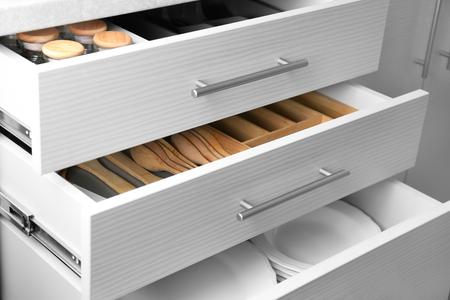Foto de Set of ceramic plates and utensils in kitchen drawers - Imagen libre de derechos