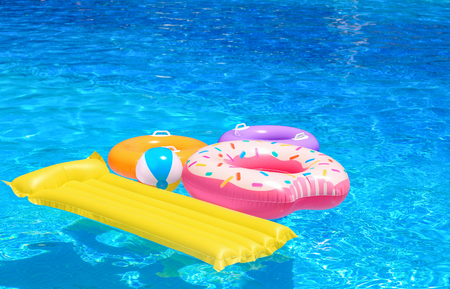 Photo pour Inflatable rings, mattress and ball in blue swimming pool - image libre de droit