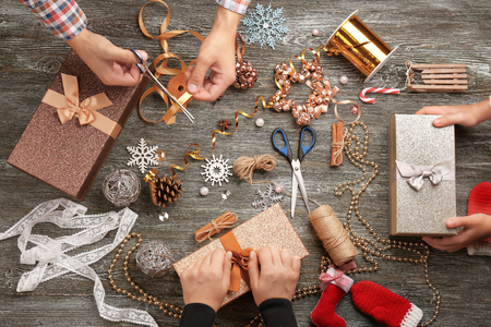 Photo for Family preparing decor for Christmas gifts on wooden background - Royalty Free Image