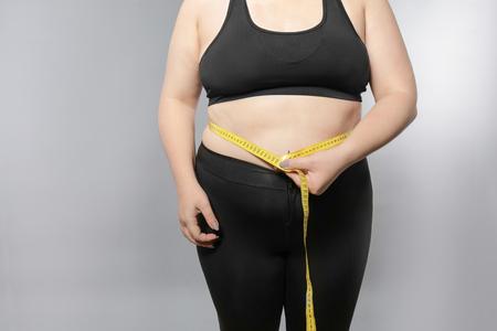 Foto de Overweight young woman measuring her belly on grey background. Weight loss concept - Imagen libre de derechos