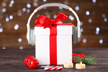 Photo pour Beautiful composition with gift box and headphones on table against blurred lights. Christmas music concept - image libre de droit