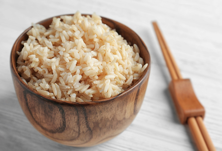 Photo for Bowl with brown rice on wooden table - Royalty Free Image