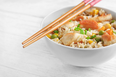 Photo pour Bowl with brown rice, vegetables and chopsticks on wooden table - image libre de droit