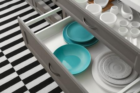 Photo pour Set of ceramic tableware in kitchen drawers - image libre de droit