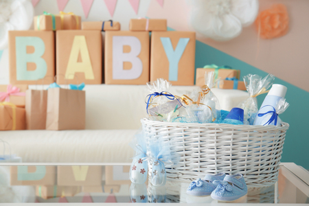 Foto de Wicker basket with gifts for baby shower party on table indoors - Imagen libre de derechos