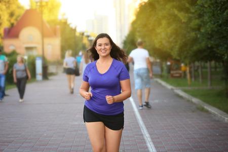 Foto de Overweight young woman jogging in the street. Weight loss concept - Imagen libre de derechos