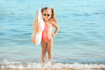 Foto de Cute little girl on sea beach - Imagen libre de derechos