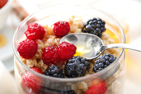 Foto de Tasty oatmeal with berries in jar on table, close up - Imagen libre de derechos