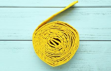 Foto de Yellow karate belt on wooden background - Imagen libre de derechos