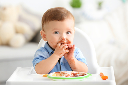 Photo pour Cute messy baby eating puree at home - image libre de droit