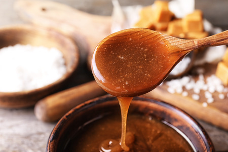 Spoon with tasty caramel sauce over bowl, closeup