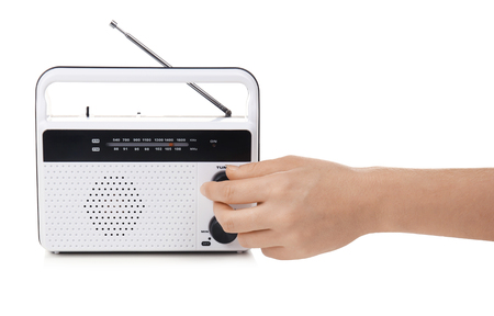 Hand of young woman with retro radio receiver on white background
