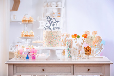 Foto de Boy or girl cake and different treats for baby shower party on table indoors - Imagen libre de derechos