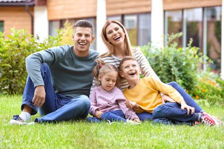 Foto de Happy family sitting on green grass in courtyard near their house - Imagen libre de derechos