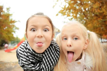 Photo pour Cute little girls in outwear outdoors - image libre de droit