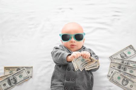 Foto de Cute boy with money on white bedsheet - Imagen libre de derechos