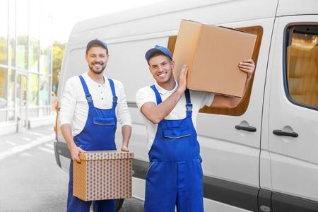 Photo pour Delivery men with moving boxes near car - image libre de droit