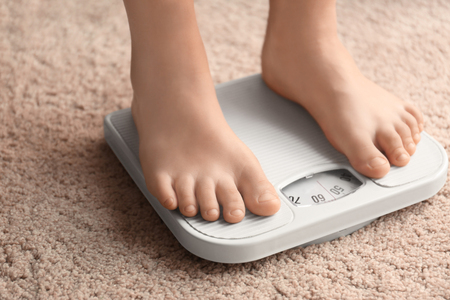 Foto de Overweight boy using scales at home - Imagen libre de derechos