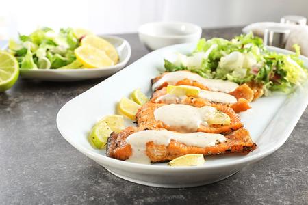 Photo pour Tasty rainbow trout fillets with sauce on plate, closeup - image libre de droit