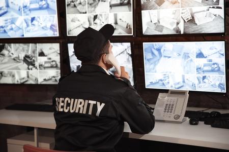 Foto de Male security guard talking by telephone in surveillance room - Imagen libre de derechos