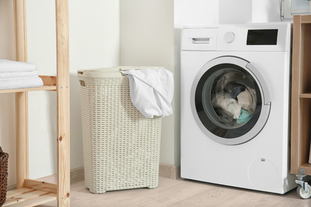 Photo pour Basket with laundry and washing machine in bathroom - image libre de droit