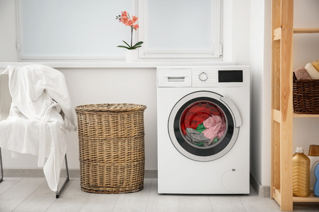 Photo pour Laundry in washing machine and basket indoors - image libre de droit