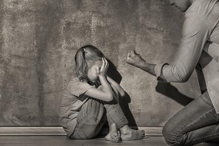 Foto de Man threatening his daughter indoors, black and white effect - Imagen libre de derechos