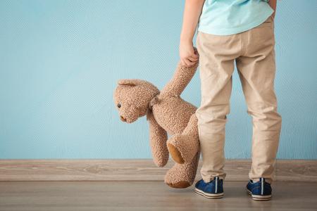 Foto de Lonely little girl with teddy bear near color wall. Autism concept - Imagen libre de derechos