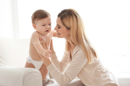 Photo pour Woman applying body cream on her baby indoors - image libre de droit